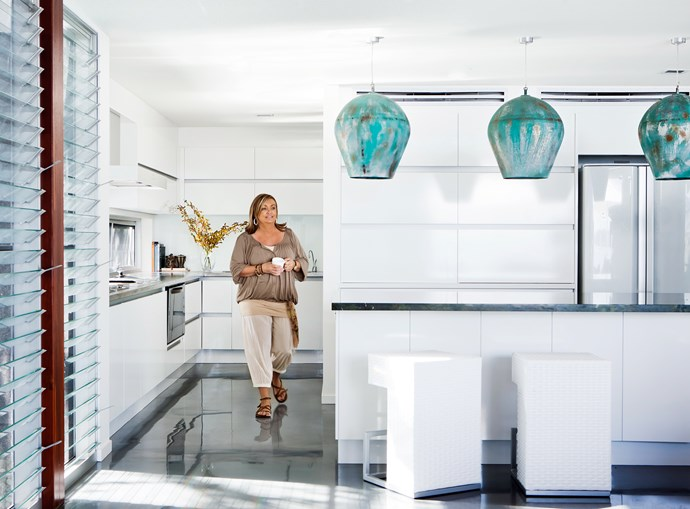 Sleek cupboards span the walls in the kitchen providing generous and unobtrusive storage. Colleen chose accent colours that reflect the ocean views.