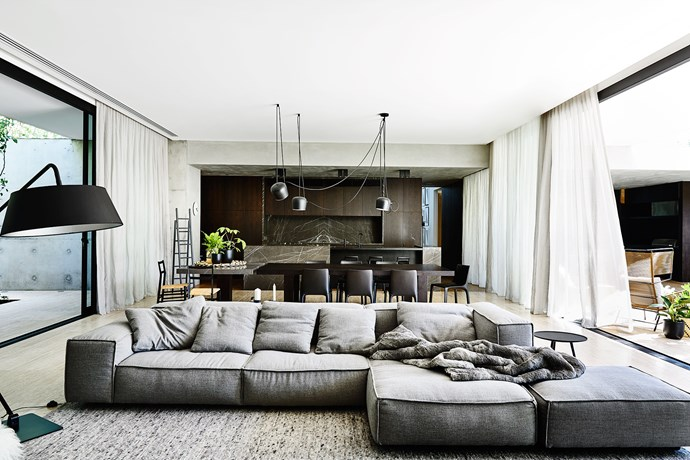 "Pietra Grigio marble enlivens the timber and concrete backdrop. This is a house whose ""dichotomy of raw and refined materials contrast and complement"", says architect John Bornas."