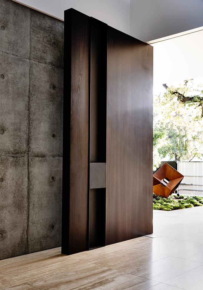 """The solid front door pivots open to reveal an impressive interior. The steel sculpture in the front garden is from [Lump Studio](http://lump.com.au/?utm_campaign=supplier/
