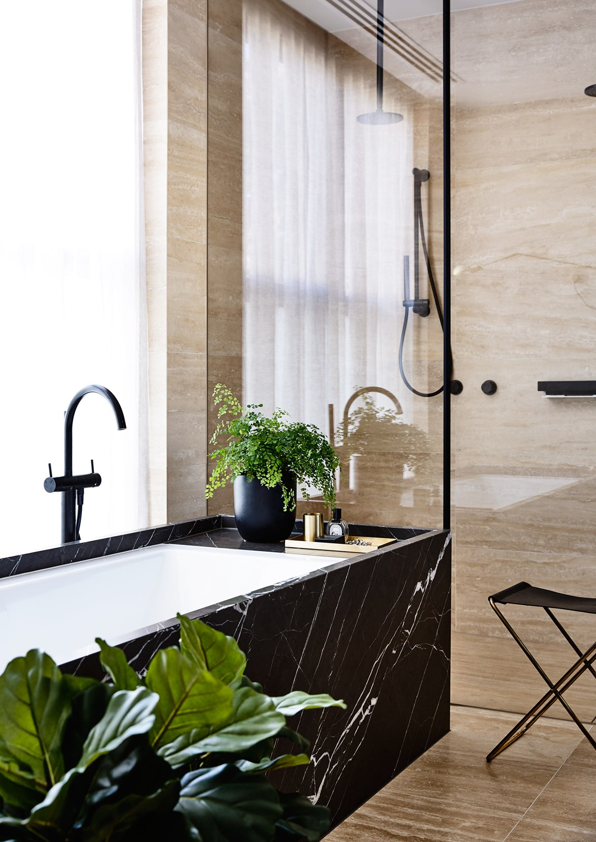 """Inset baths and indoor plants are a match made in heaven. Take for example, this luxurious but understated marble and travertine space that belongs to builder [Bear Agushi](https://www.homestolove.com.au/dynamic-duo-pair-up-for-a-stunning-new-build-3680