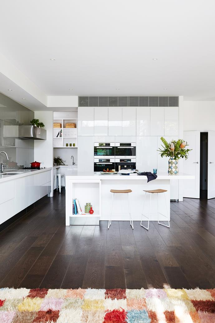 The generous kitchen is perfectly positioned in the corner of the open-plan area, within sight of the children's living room, family room and pool and garden beyond.
