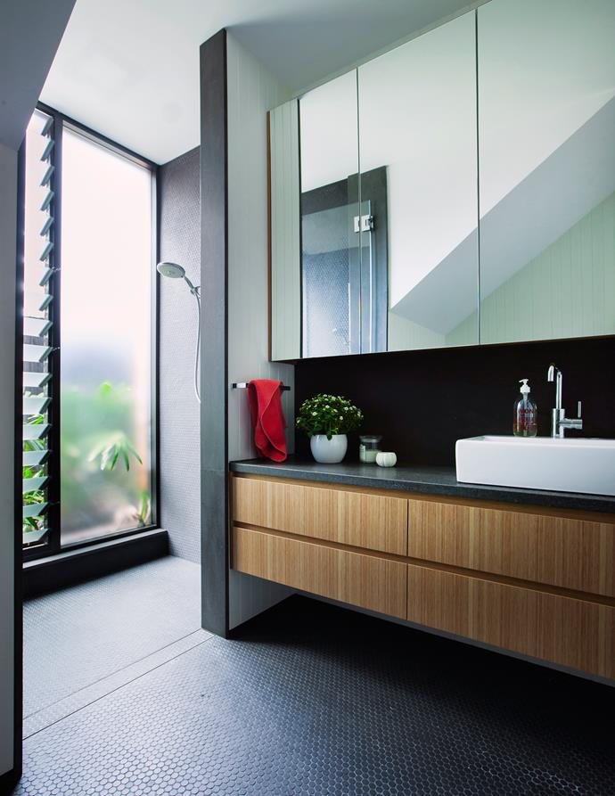 In the main bathroom, frosted glass and mirrored surfaces lighten the dramatic effect of black mosaics.