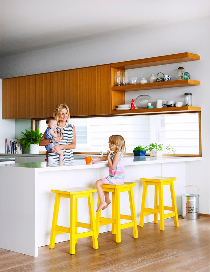 Owner Libby with one-year-old Billie and Lila, three, in the easy-care layout that combines sandblasted oak veneer and polyurethane finishes.