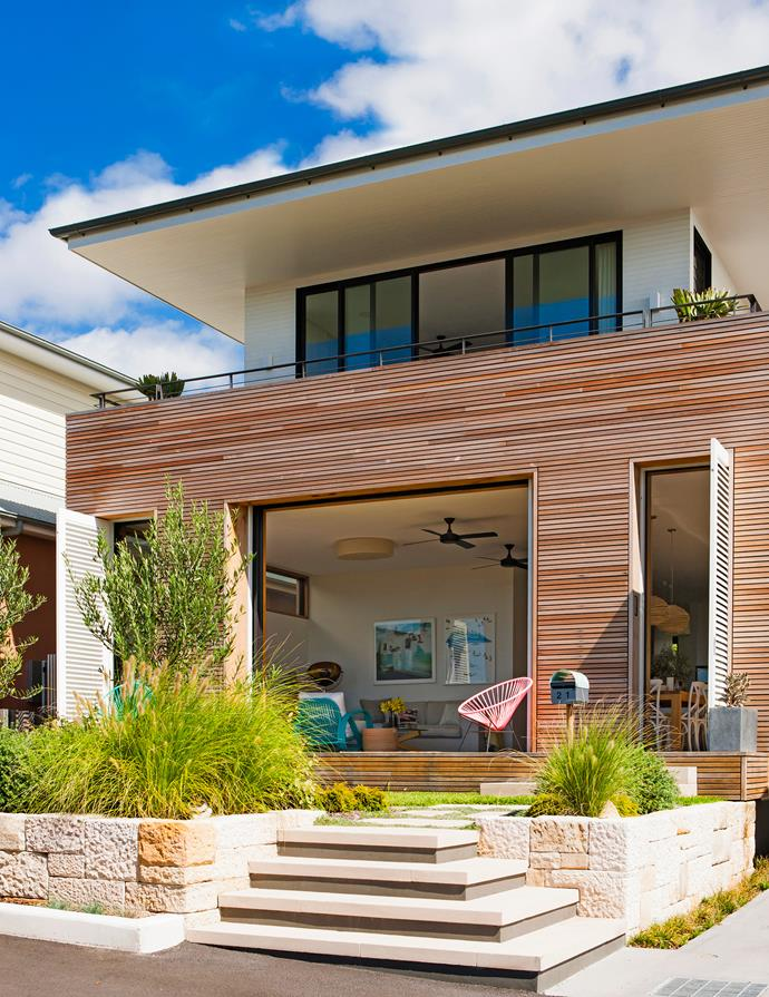 The new six-bedroom two-storey home presents a warm, welcoming face with its cladding of western red cedar battens. Instead of a high front fence, there's a low sandstone wall.