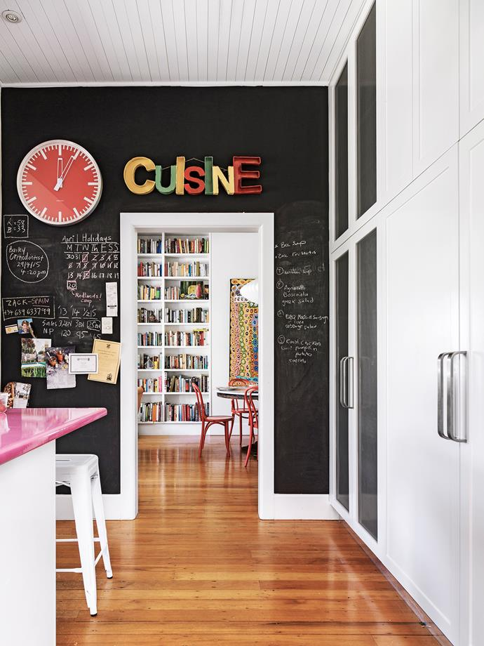 A chalkboard feature wall acts as a noticeboard as well as a grounding counterpart to splashes of bright colour.