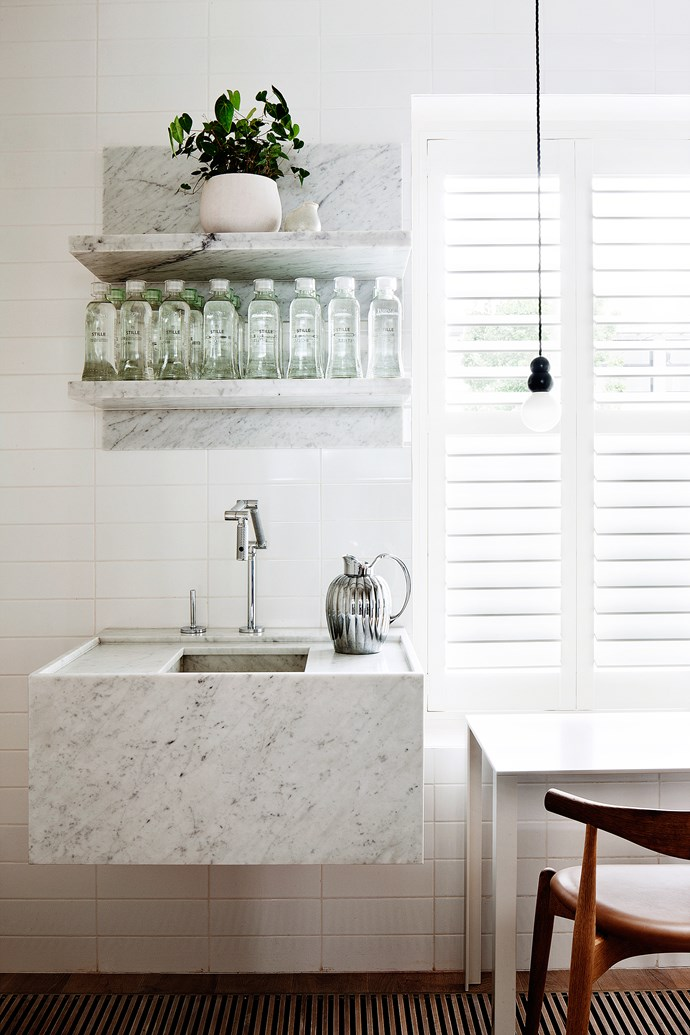 "The semi-divided kitchen space includes a separate custom-designed baptismal-like basin and shelving in Bianca Carrara slabs. Floor-to-ceiling glossy white [wall tiles](http://www.homestolove.com.au/6-creative-ways-to-use-tiles-in-your-home-3419|target=""_blank"") assume the place of a traditional splash back."
