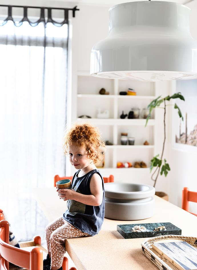 "Simone's daughter sits under a Swedish ""Bumling"" pendant light from the 1970s, one of the pieces that dictated the whole interior look."