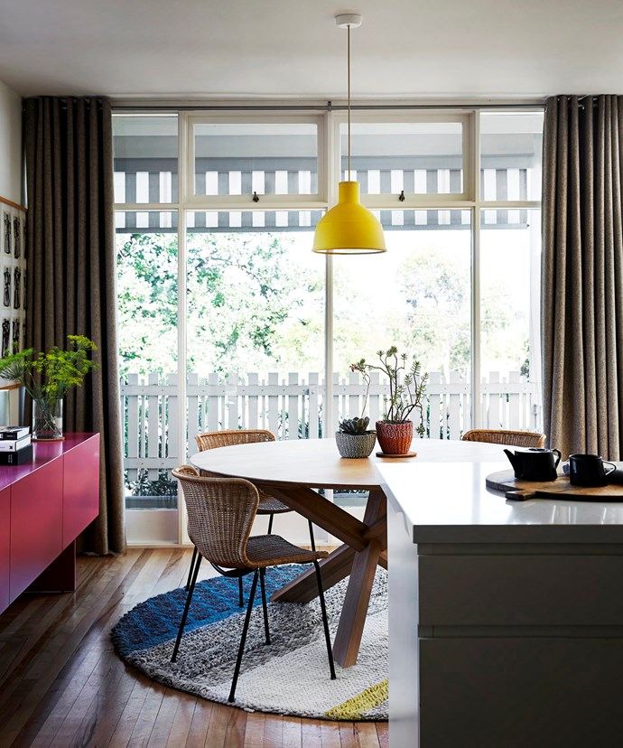 A round table works to maximise space in the dining zone and allows for easy passage without any sharp corners. More colour is injected via a stripy rug and custom-made fuchsia sideboard.