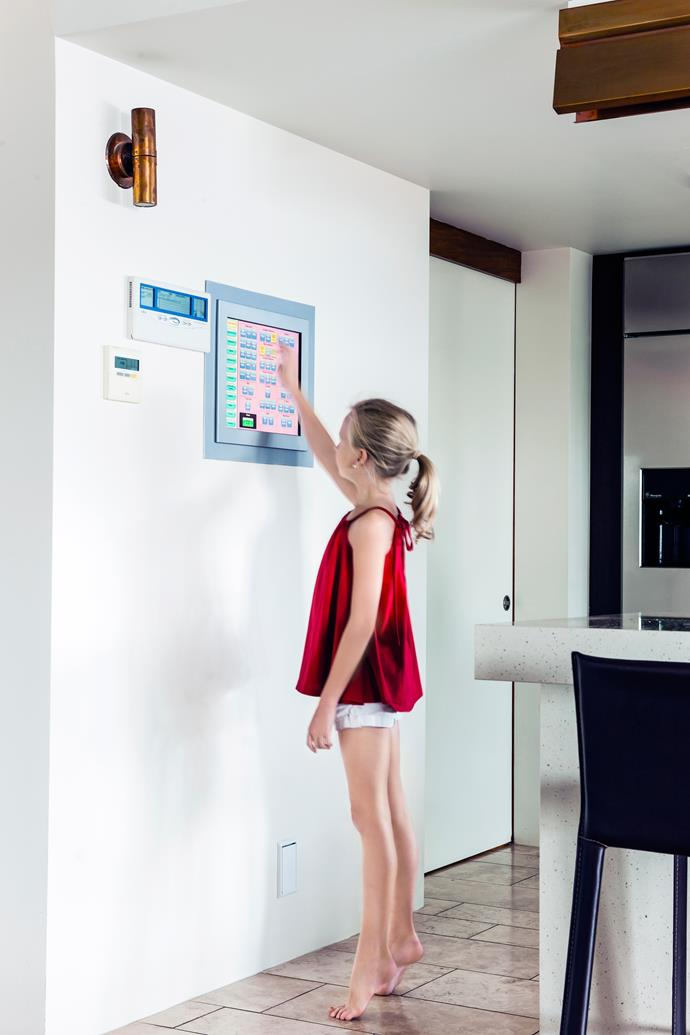 """A C-Bus control hub drives the home's automated systems. In sleep mode, the screen displays family [photographs](http://www.homestolove.com.au/how-to-care-for-photographs-3580/?utm_campaign=supplier/ target=""""_blank"""")."""