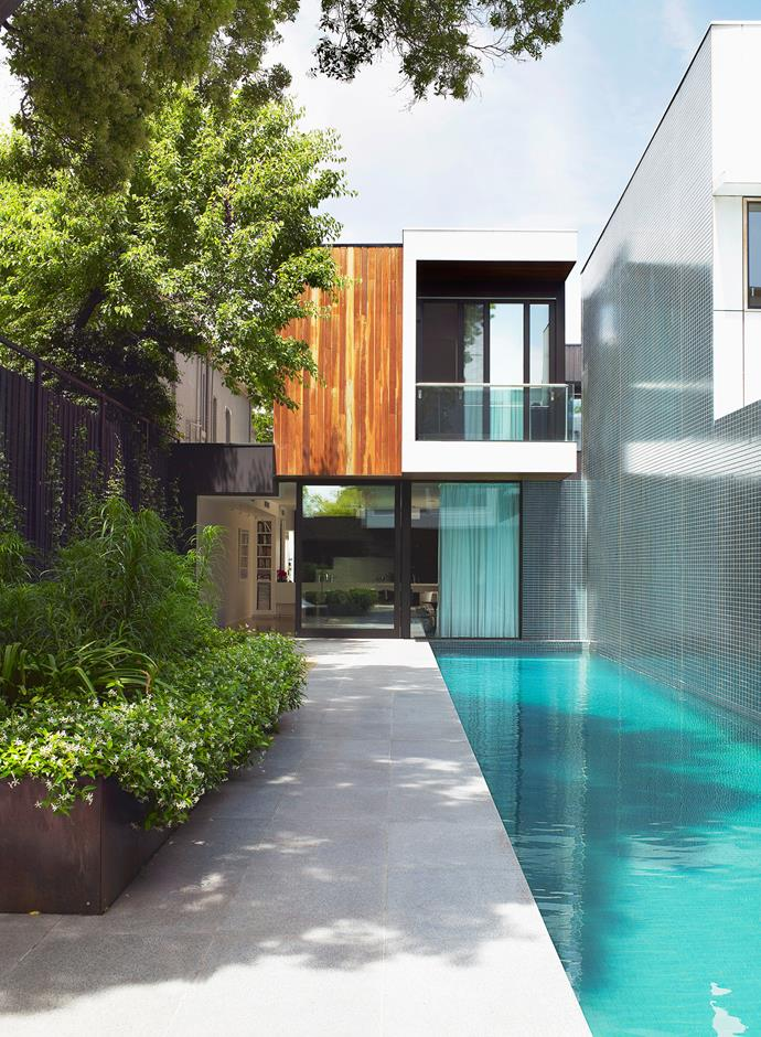 "The homeowners wanted a 25m pool as well as a garden, so they settled on a 3m-wide lap pool which extends right to the living room wall. The adjacent external walls of the home are covered in ceramic tiles with a silvery-green metallic glaze, a colour chosen to create a strong relationship with the garden, says co-director of [McBrideCharlesRyan architects](http://www.mcbridecharlesryan.com.au/#/news/|target=""_blank""), Debbie Ryan."