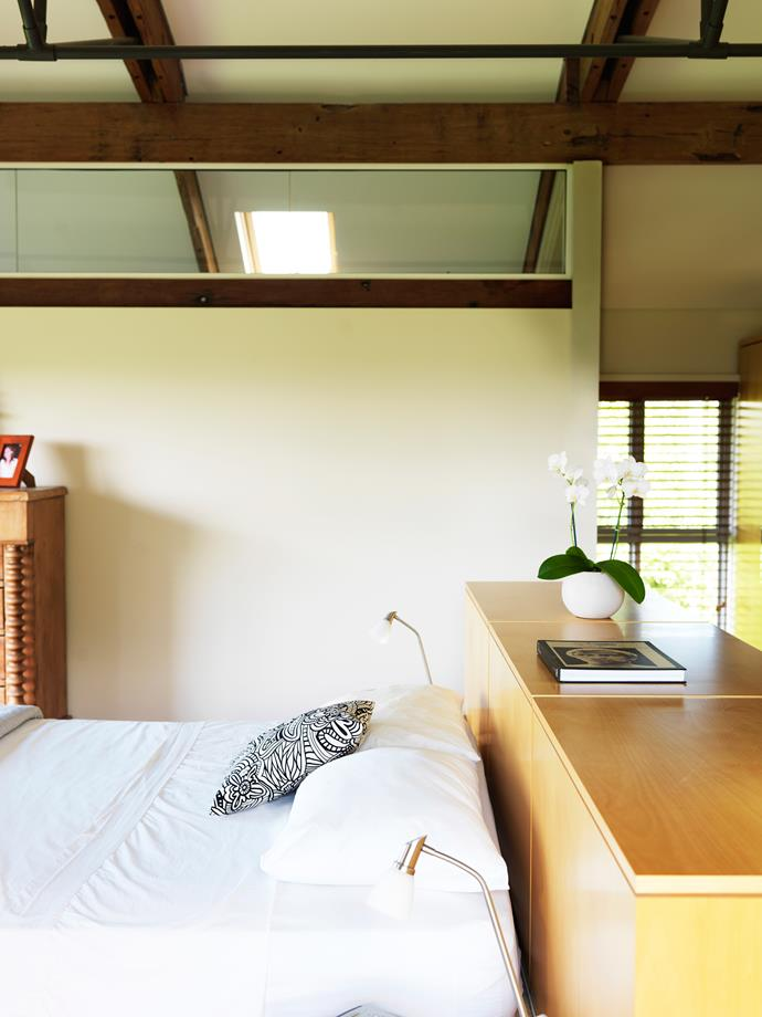 """In the main [bedroom](http://www.homestolove.com.au/how-to-create-a-bedroom-retreat-3771 target=""""_blank""""), joinery doubles as a bedhead. A sliding screen allows a view down to the living area and helps air to circulate."""