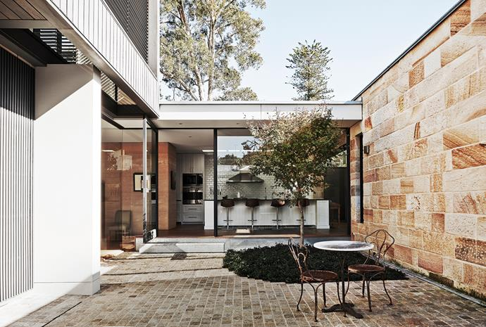A glass breezeway wraps around a north-east facing courtyard and links the original cottage to a two-storey modern addition.