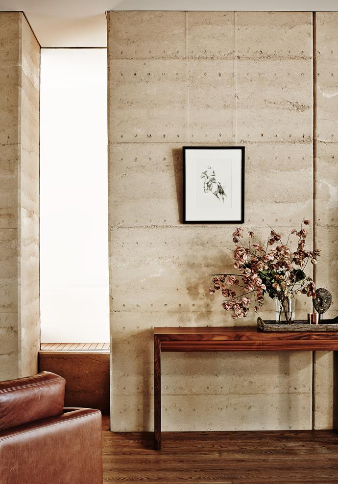 The textured rammed-earth wall, sourced to match the cottage's distinctive pink sandstone, runs the full length of the living space and creates a back-of-house services area.