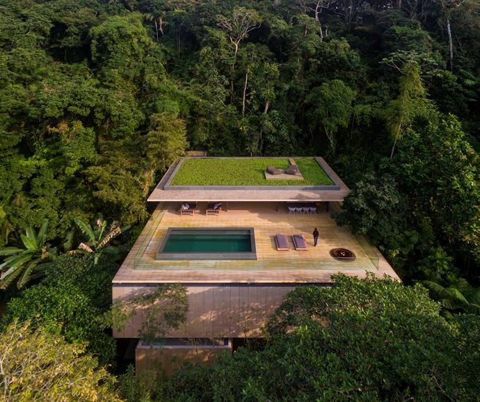 With wooden decking and a landscaped roof, the house allows its natural surrounds to feel largely untouched. The top floor has views of the ocean and contains the kitchen, living and dining areas - perfect for entertaining. *Photo: Fernando Guerra*