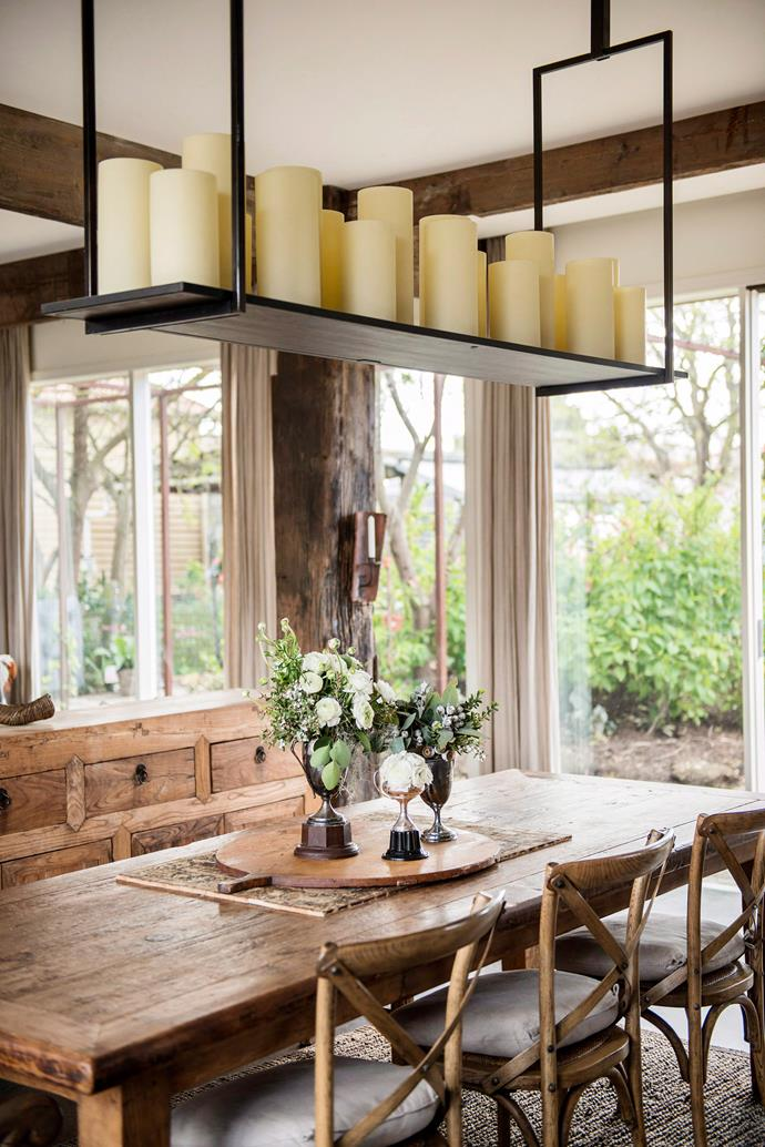 Mix similar timbers for a timeless look. Break it up with greenery and accessories, like these candles hanging above the table. Photo: bauersyndication.com.au