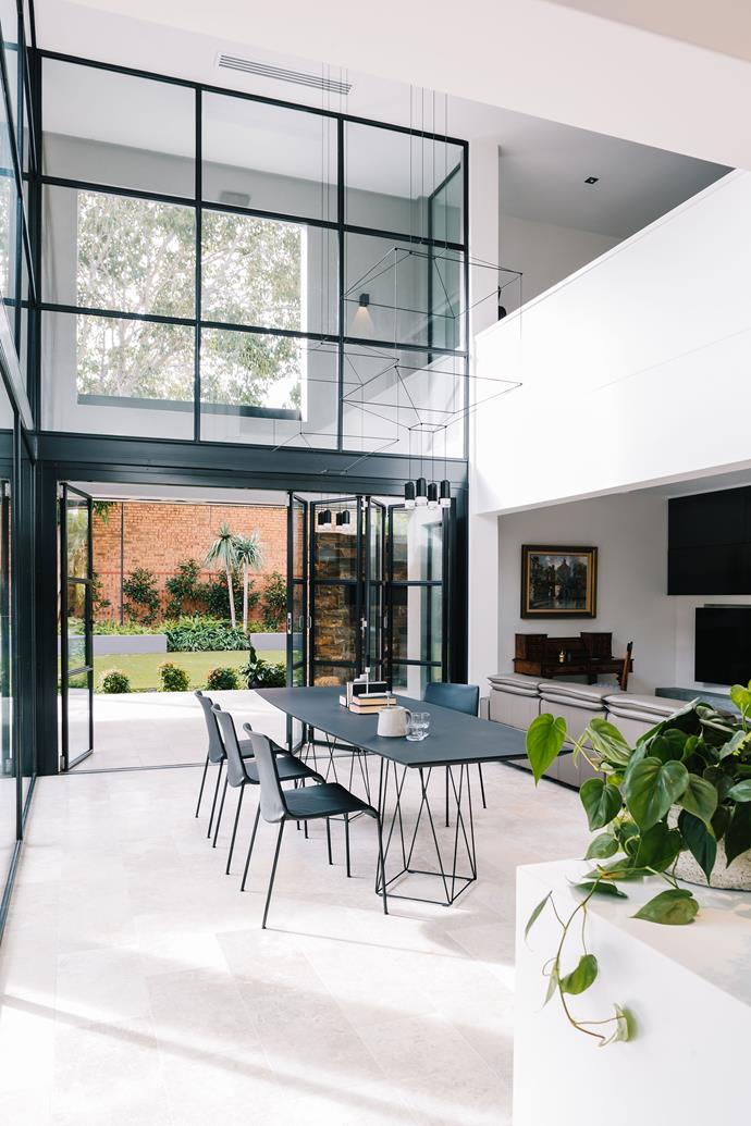"""In the Frame by [Williams Burton Leopardi](http://designbywbl.com.au/ target=""""_blank"""").  A 1980s Adelaide home was pared back to its simplest form to reveal the beauty of the original architecture. In the dining room, Williams Burton Leopardi capitalised on a double height space and enhanced the connection to the garden by framing the view with slim steel frame windows at ground level that span up to the ceiling. Limestone flooring knows no barriers and encouraging life to spill outdoors into the pavilion space. *Photography by Christopher Morrison.*"""