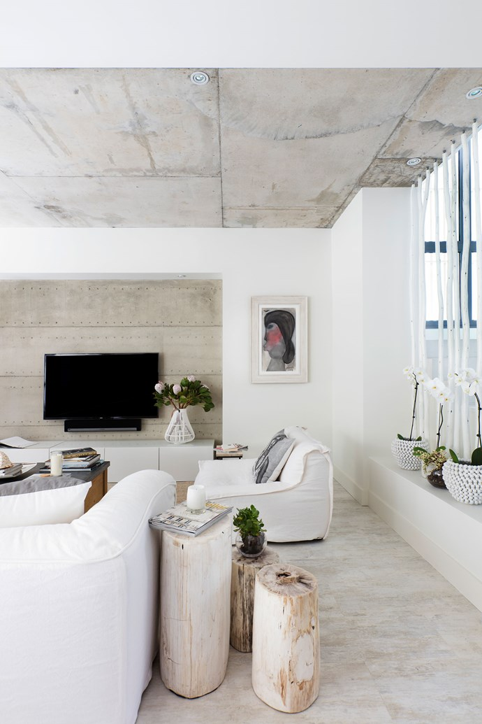 """Softly Does It by [Blupeter Homestore](http://www.blupeter.com.au/ target=""""_blank""""). Perfectly pale yet wonderfully warm: this Perth living room is a celebration of tonality and texture. A grey rammed-earth feature wall pairs well with the raw concrete ceiling and white timber-look floor tiles. Painted timber poles function as a balustrade and bring yet more organic beauty to the room, says interior designer Adri-Ann Brown. Raw-linen slipcovers on the sofa and log-look side tables complete the look and ensure texture takes top billing. *Photography by Bo Wong. Styling by Anna Flanders, stylist's assistant Anisah Nasir.*"""