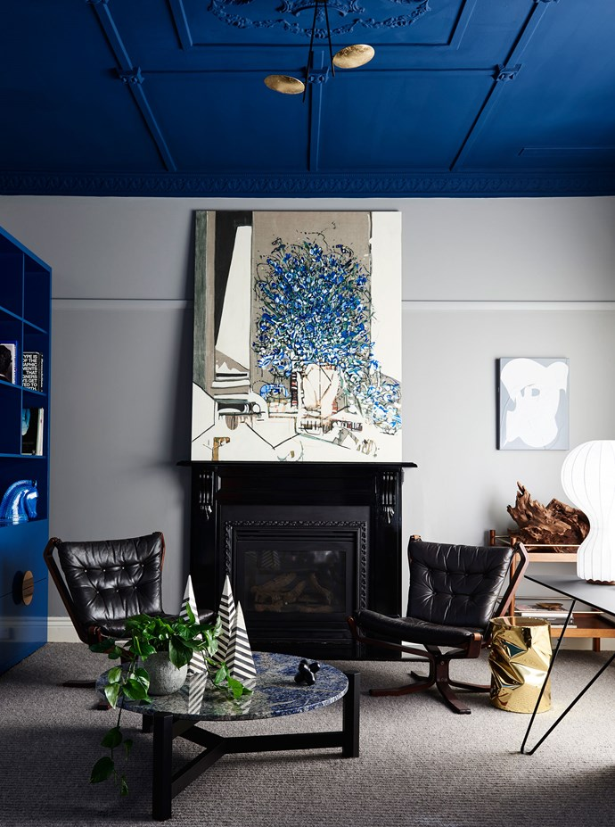 """Above And Beyond by [Chelsea Hing](http://chelseahing.com.au/ target=""""_blank""""). Beginning with the elaborately decorative ceiling, interior designer Chelsea Hing turned to traditional European interiors for inspiration, and painted the ceiling (and double doors) a cosseting deep blue. The room is used as a home office, where the owner often hosts clients, so it needed to be both functional and aesthetically pleasing. Comfortable seats for fireside drinks are counter-balanced by the functional desk, positioned by the window for optimum natural light, and concealed storage that hides books, files and the printer. *Photography by Eve Wilson.*"""