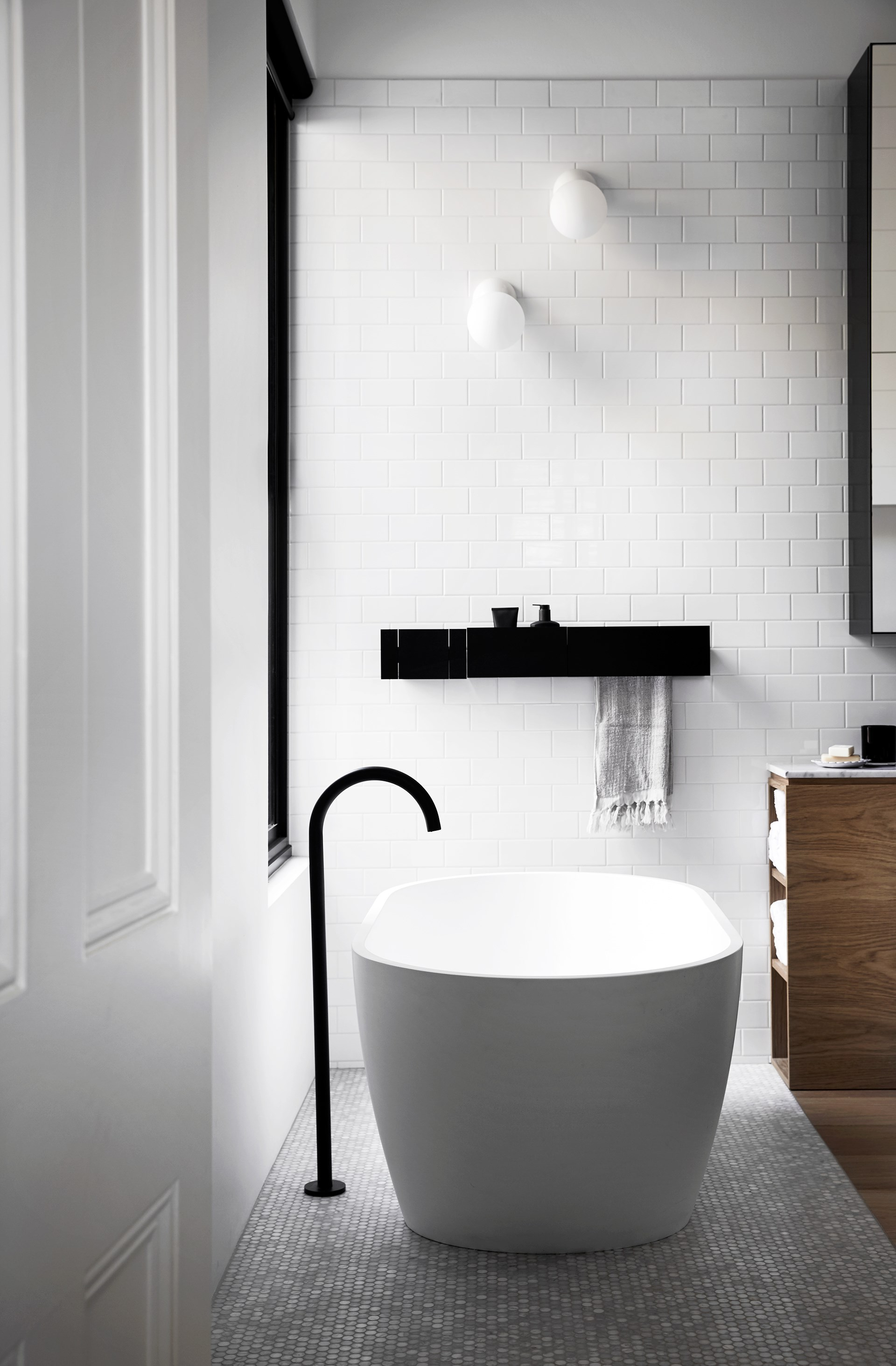 """A white bath and black spout are a simple yet striking pairing in the bathroom of this [renovated Edwardian house](http://www.homestolove.com.au/a-light-hearted-luxury-home-3944 