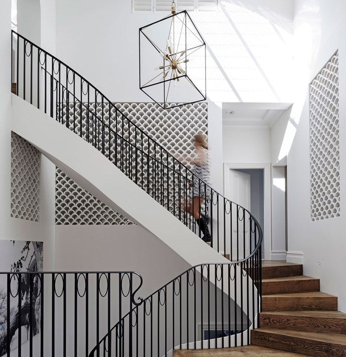 """Scale The Heights by [Luigi Rosselli Architects](http://luigirosselli.com/ target=""""_blank""""). Drawing inspiration from classic New York apartments and hotels, Luigi Rosselli has delivered a grand new staircase and entry to this Sydney home. """"It acts as a link between the street and the private levels of the home, setting the scene for the beautiful finishes and spaces beyond."""" An elliptical skylight echoes the curve in the staircase and allows light to flood in from three storeys above. The curved stairs are constructed from American oak engineered timber and the balustrade is steel. Picking up on the fish-scale pattern that's repeated through the home, halved terracotta pipes create a striking decorative element in the foyer. *Photography by Justin Alexander.*"""