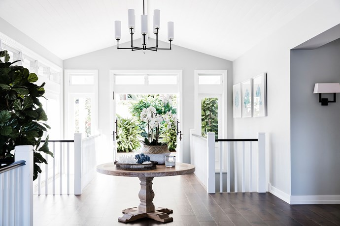 """Open Approach by [Tonka Andjelkovic Design](http://www.tonkaandjelkovicdesign.com/ target=""""_blank""""). Extra-wide European oak floorboards lead guests in from the front door of this home in Sydney's Sutherland Shire. """"I've positioned the table centrally to create a sense of arrival,"""" says interior designer Tonka Andjelkovic. """"As you walk around it you're greeted with views of either the nearby waterfront or the pool. This entire renovation was all about framing the views."""" Half-strength Resene Foggy Grey was chosen for the walls and paired with half-strength Resene Sea Fog on the doors and handrails. *Photography by Maree Homer.*"""