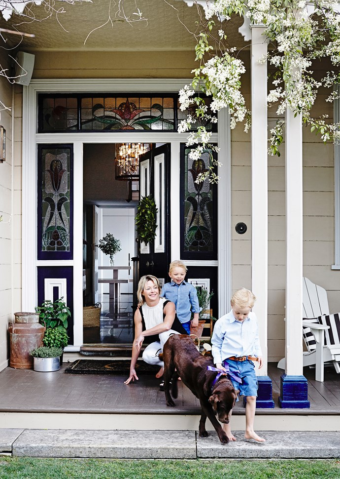 Owner Jo and sons Josh and Angus romp with River the chocolate labrador. Their home, Vernon, is listed in the Tasmanian Heritage Register for its cultural and historical significance.