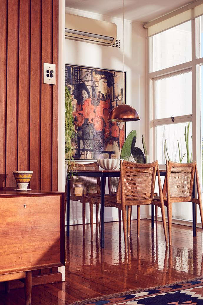 "The 1963 Featherston ""Delma"" table by Aristoc is used for intimate dinners with friends. ""It only seats four, but it's a nice place to sit with a lovely view out towards the pool,"" Michelle says. The vintage chairs were designed by John Duffecy (1919-2002) and the copper pendant was a garage-sale find."
