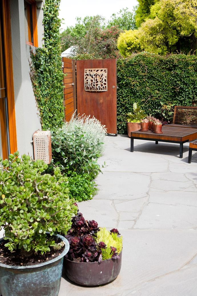 "Christine, the homeowner, loves silver, purple, oranges and acid-green plants, so this colour palette inspired Kate's choices. ""Oversized slate crazy paving stones make the space feel larger than it is,"" says Kate."