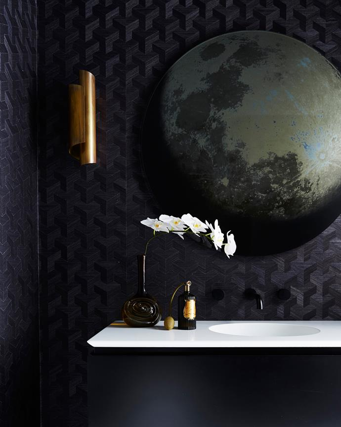 """Visitors are always wowed by the edgy powder room. """"The black wallpaper, black tapware and black ceiling give the powder room a moody ambience, and there's the concealed door that opens up to the hidden laundry,"""" says Poppy. """"It adds an element of the unexpected, so we call it the Bat Cave!"""" The brass wall lamp, bought online at [1stdibs.com](https://www.1stdibs.com/