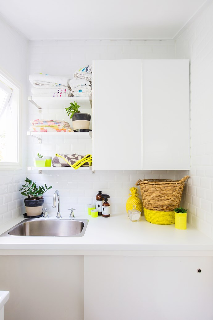 Custom-built cabinets and Ikea shelves maximise useful space in the laundry.