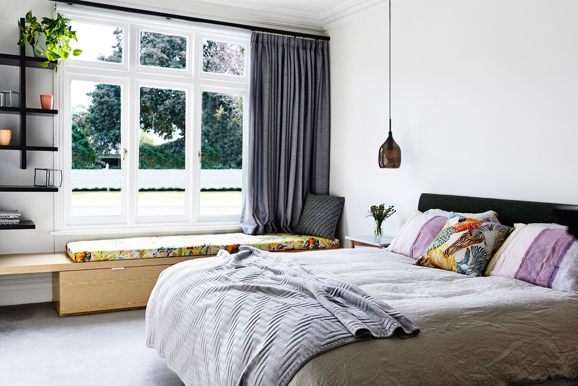 Woven curtains in Warwick Fabrics Chios Asphalt try in with the soft furnishings to create a relaxed and inviting feel in this bedroom. Photo: Derek Swalwell