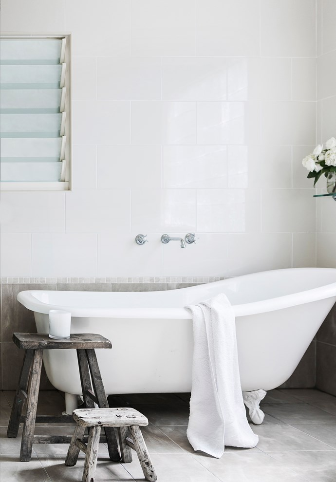An original rolltop bath adds femininity in the modern tiled bathroom.