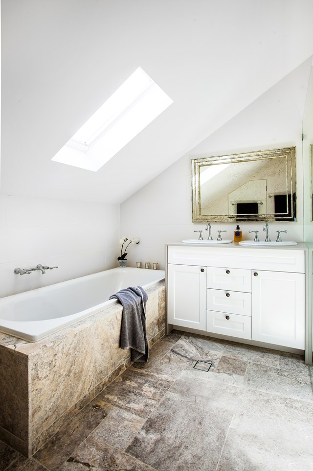 "During the [renovation of this 1930s era home](https://www.homestolove.com.au/house-renovation-finds-the-balance-between-old-and-new-4099|target=""_blank""), the owners converted the attic into a luxurious bathroom. They opted for a bath framed in travertine tiles. To create visual interest, the tiles were cut in a variety of different sizes and laid in a traditional French style. *Photo: Scott Hawkins  / Story: Australian House & Garden*"