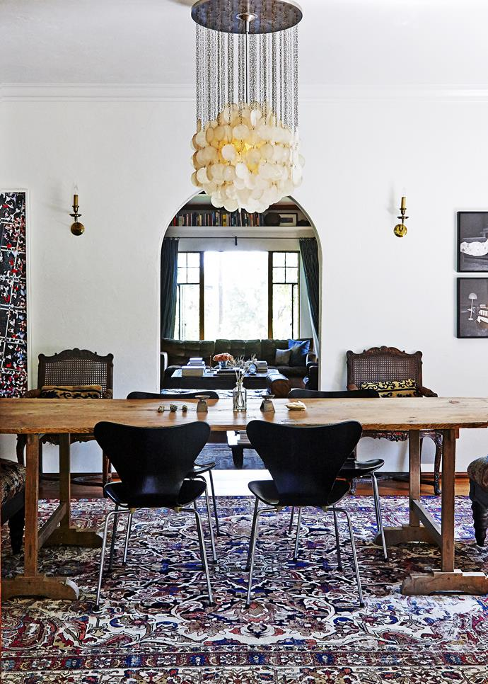 """The archway softens the lines of the dining room and frames the living room beyond.  A Verner Panton """"Fun 4DM"""" mother-of-pearl hanging lamp over the dining table provides a feel of understated luxe and a contrast to the rustic table."""