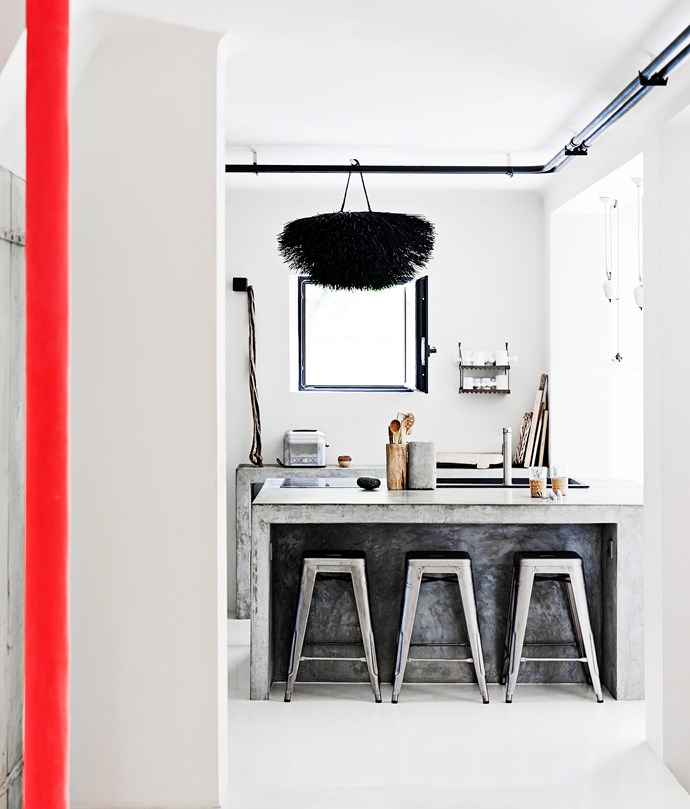 """The kitchen is industrial while still being warm and inviting. A hanging nest-like decoration creates an interesting contrast to the concrete benchtop and steel """"Tolix"""" barstools."""