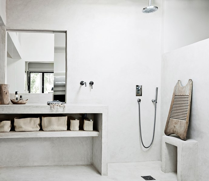 The ensuite features a long benchtop with an integrated sink – a similar shape to the kitchen benchtops. Wooden accessories soften the rendered look.