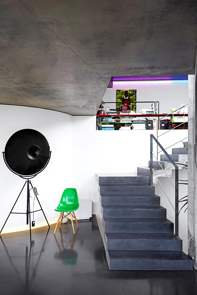 """A cast concrete staircase leads from the dining room to the living area. The striking sculptural Fortuny """"Moda"""" floor lamp creates an impact while the Eames chair provides another pop of colour."""