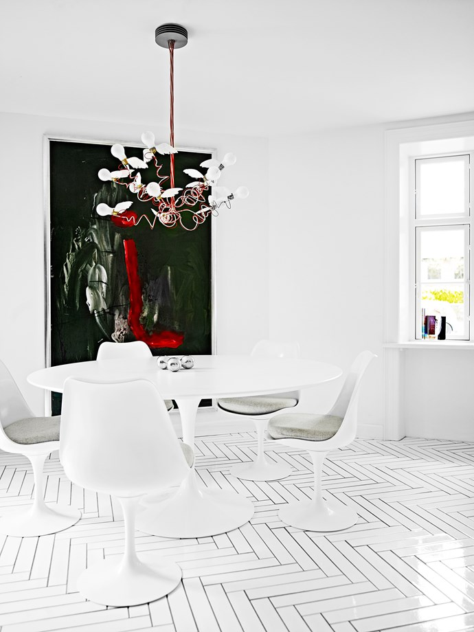 """The dining room is furnished simply with an Eero Saarinen """"Tulip"""" table and chairs set. Red accents in the Marco Evaristti painting and the Ingo Mauers chandelier lift the monochrome scheme."""