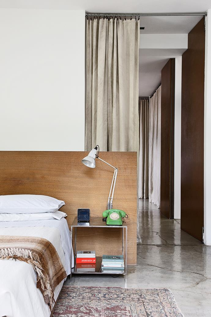 In the bedroom, the white and concrete palette is softened with organic timber furniture, tribal rugs and floor-to-ceiling curtains, which gently sweep the floor.