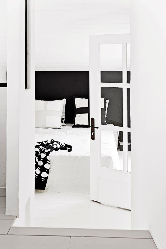 In the master bedroom, a black feature wall acts as a bedhead while echoing the black door downstairs. It provides a smart contrast to the white bedlinen and graphic cushions, designed by Angelica.