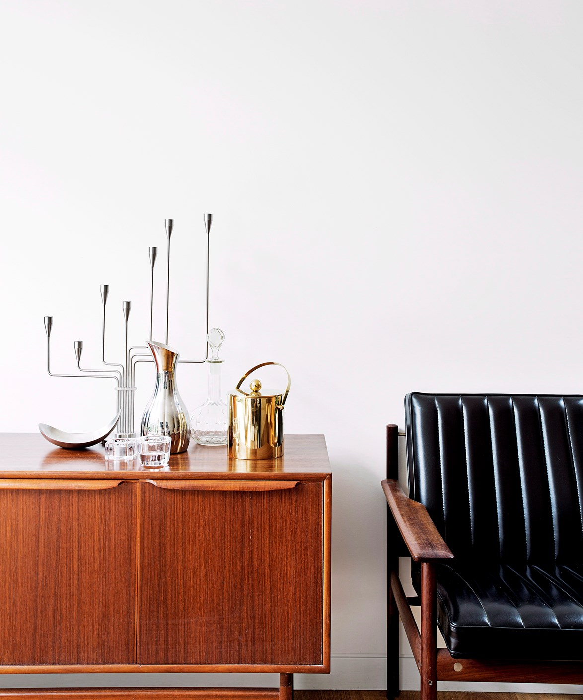 Vintage candleholders in hourglass shapes – a 1950s motif – are combined with classic Danish furniture and a brass ice bucket for a luxe mid-century touch. *Photo:* Felix Forest / bauersyndication.com.au