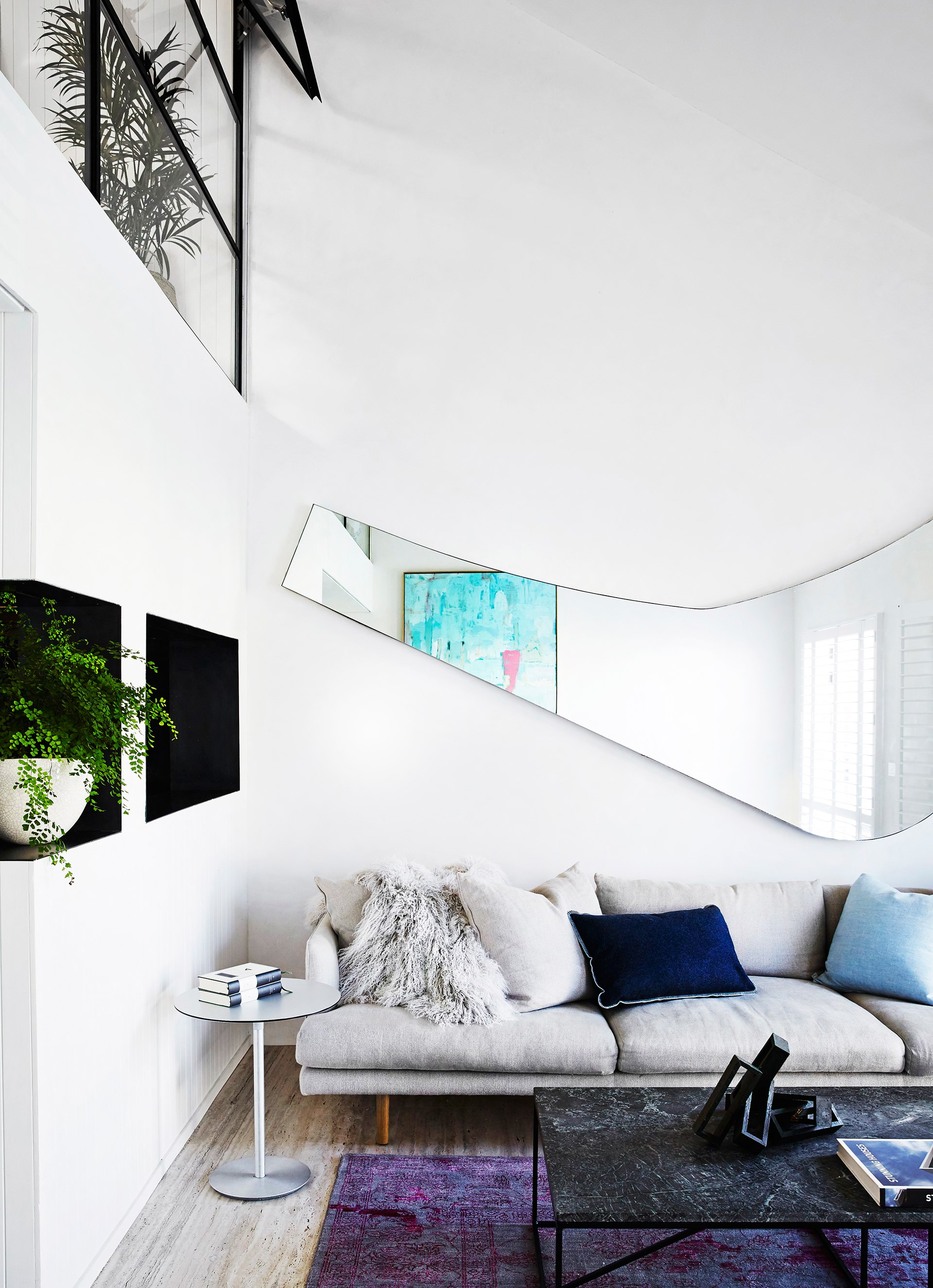 A fresh white palette and high ceilings creates a calming atmosphere in this [artistic Melbourne living room](http://www.homestolove.com.au/renovation-of-a-victorian-home-in-east-melbourne-4199), tucked away in a cosy corner to create a seclude retreat. Photo: Sharyn Cairns / real living