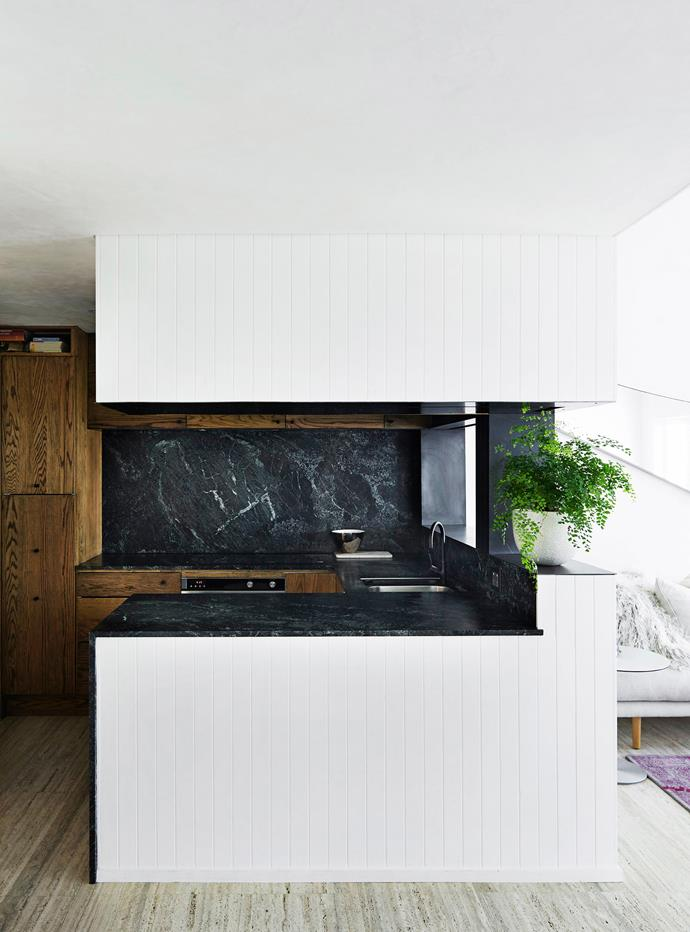 "The site of the existing kitchen remained but everything else was changed. An ebony stain was applied to solid American oak joinery; the [kitchen benchtops](http://www.homestolove.com.au/how-to-pick-the-right-kitchen-benchtop-2655|target=""_blank"") are green marble. Though the kitchen is dark, Andrew says, ""Everything that happens in it becomes more theatrical. It also works in contrast to the white spaces of the apartment."""