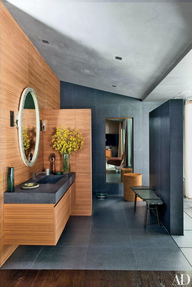 """This modern master bathroom in John Legend and wife Chrissy Teigen's Los Angeles home combines natural contrasting finishes such as dark stone and honey coloured teak for a bold yet calming space. Photo via: [Architectural Digest](http://www.architecturaldigest.com/ target=""""_blank"""" rel=""""nofollow"""")."""