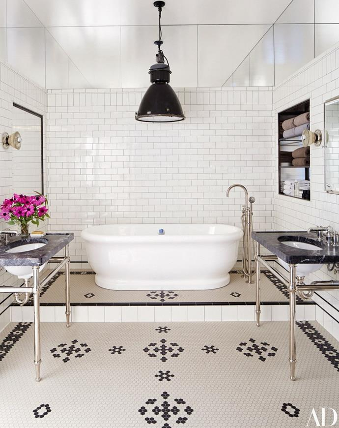 """Meg Ryan's vintage-industrial style bathroom looks like something off a movie set. Classic white subway tiles complement traditional mosaics while the exposed chrome vanities and large industrial pendant make a bold statement. Photo via: [Architectural Digest](http://www.architecturaldigest.com/  target=""""_blank"""" rel=""""nofollow"""")."""
