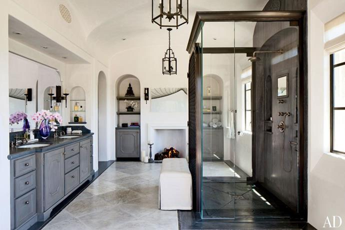 """This opulent and very spacious bathroom in supermodel [Gisele Bündchen and Tom Brady's LA home]( http://www.architecturaldigest.com/gallery/gisele-bundchen-tom-brady-los-angeles-eco-conscious-home-slideshow#16 target=""""_blank"""" rel=""""nofollow"""") has all the luxury trimmings – marble benchtop and floor, chandelier-style pendant lights and an open-fireplace (of course!). Photo via: [Architectural Digest](http://www.architecturaldigest.com/ target=""""_blank"""" rel=""""nofollow"""")."""