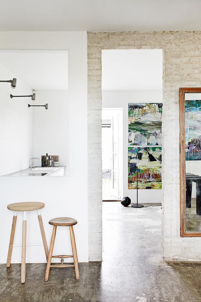 The wall separating the kitchen from the dining area is part finished in white render and part left as raw brick. The wooden stools and timber-framed mirror add warmth.