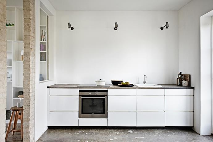The kitchen design is modern but rustic to suit the decorative tone of the rest of the home. The white cabinetry appears to float between the concrete countertop and floor.