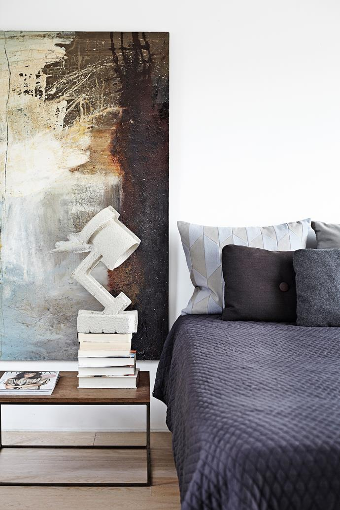 The master bedroom is moody and simplistic with the painting Migrating Birds as the focal point.