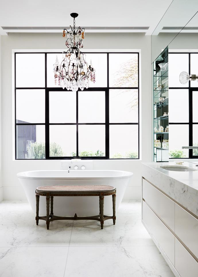Custom metal windows by ADS Design strike a clean look in the bathroom along with bath and tapware by Rogerseller, contrasting with the 19th century French fruit chandelier bought on a Kings Road antiquing expedition and the country French bench seat.